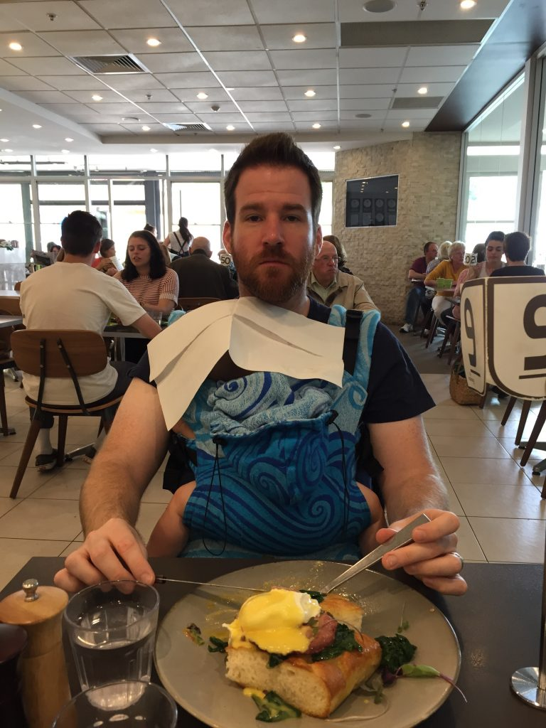 Babywearing and eating. Some struggle with it more than others. Dad babywearing and eating lunch with napkin over baby's head.