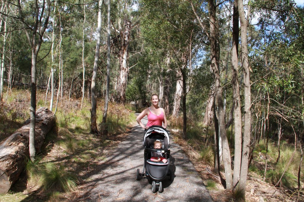 Tidbinbilla Nature Reserve. Mom stands under trees with baby in stroller.