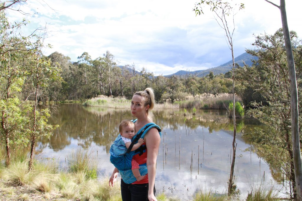 Mom wears baby and both make a sad face in Tidbinbilla Nature Reserve.